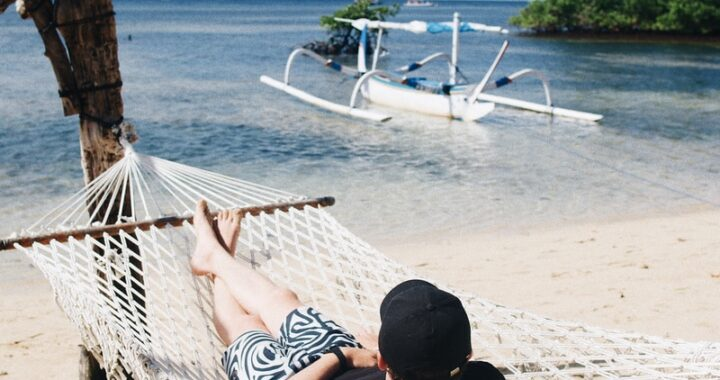person lying on hammock during daytime