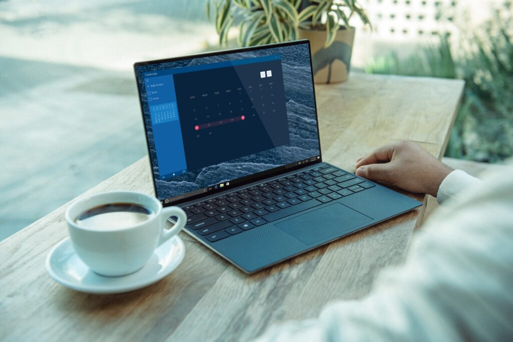 person using black laptop computer on brown wooden table